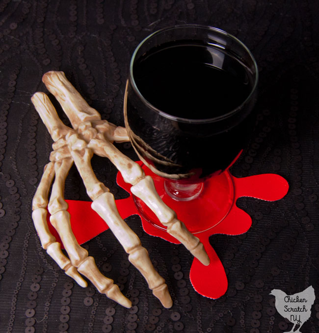 skeleton hand holding glass of dark liquid on top of bright red blood spatter coaster