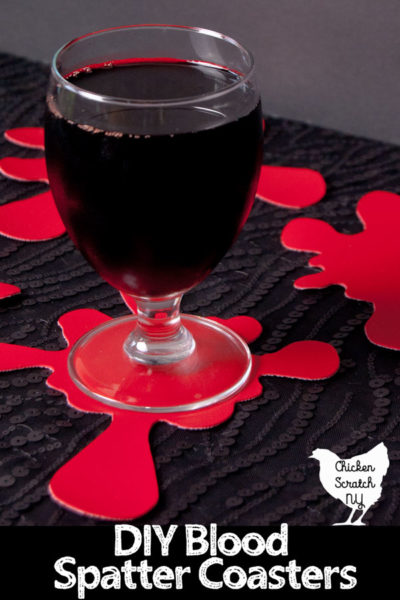 glass of red juice on a red vinyl hand made coaster shaped like a blood splatter