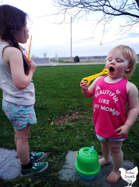 two little girls in summer clothes blowing bubbles from an untippable bubble solution holder