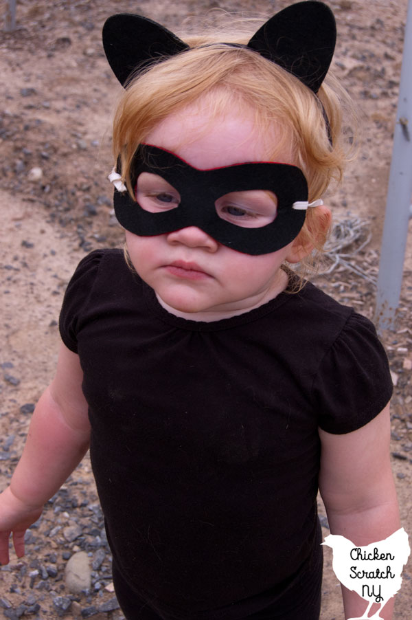 little blonde girl in black shirt with black superhero mask and black cat ears