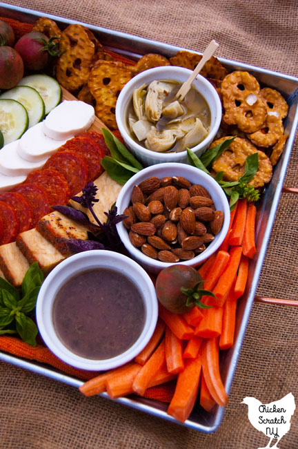 a metal tray with a cutting board with mozzarella cheese, feta cheese, pepperoni, cherry tomatoes, carrot sticks and toasted bread, pretzel thins, cucumber slices, marinated artichoke hearts, almonds and vinaigrette with fresh basil