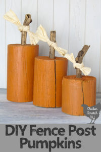 three pieces of round fence post painted orange with sticks glued to the top to make fence post pumpkins