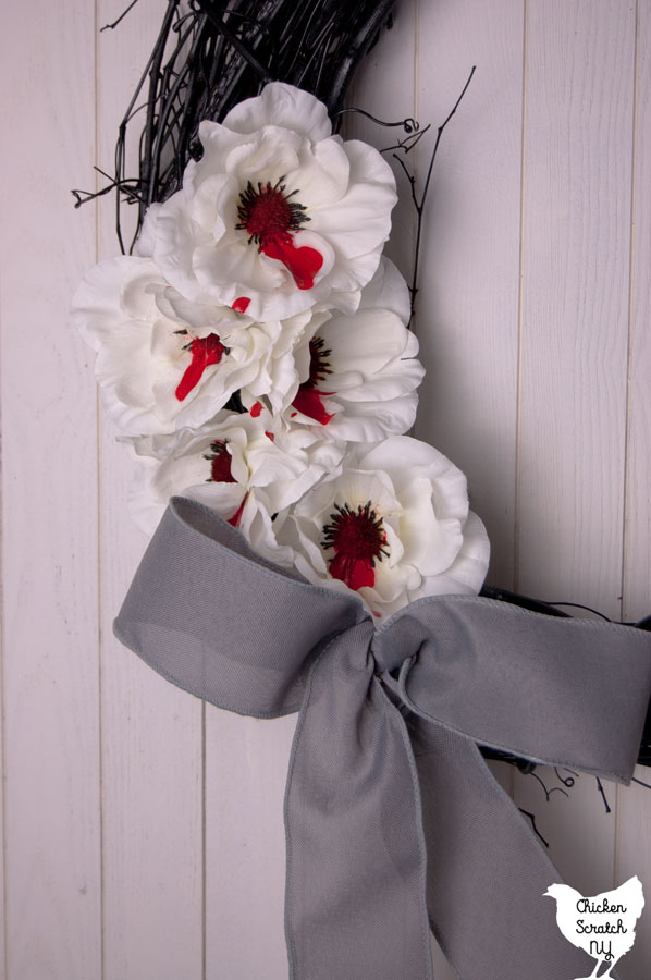 black grapevine wreath with bleeding white flowers and a grey bow on a white wooden background