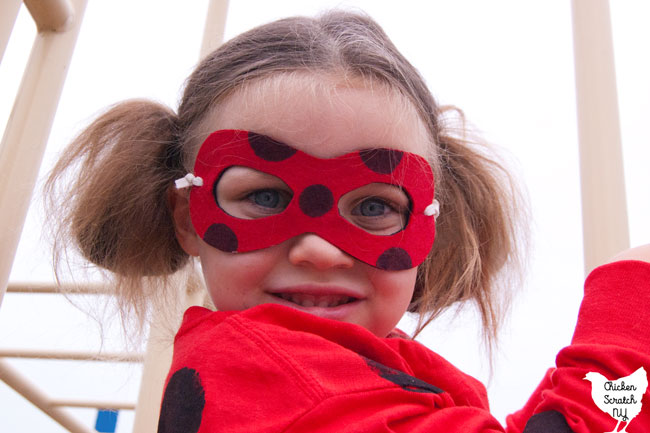 little girl wearing a homemade miraculous ladybug costume and mask