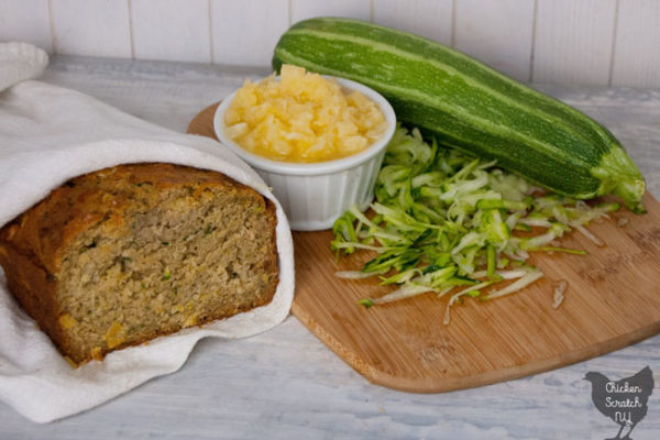 homemade sliced pineapple zucchini bread wrapped in a white tea towel in front of a cutting board with shredded zucchini and crushed pineapple in a white dish