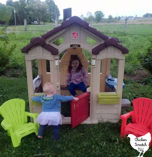 two little girls in a plastic plastic playhouse with little plastic Adirondack chairs