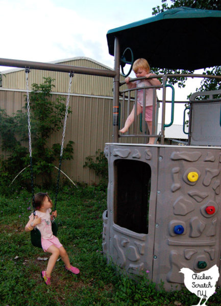 two girls in pink shirts and shorts playing on a large back yard metal swing set
