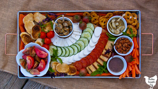 bowl of sliced red and purple tomatoes on a metal tray with a cutting board with mozzarella cheese, feta cheese, pepperoni, cherry tomatoes and toasted bread, pretzel thins, cucumber slices, marinated artichoke hearts, almonds and vinaigrette with fresh basil