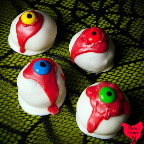 four red velvet oreo truffles dipped in white candy melts with a red drizzle and a blue, yellow, green and orange m&m eye with a black pupil on a green surface with a black spiderweb pattern
