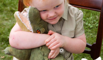 young blonde girl in a khaki saffri shirt hugging a stuffed crocodile for a Steve Irwin Halloween Costume