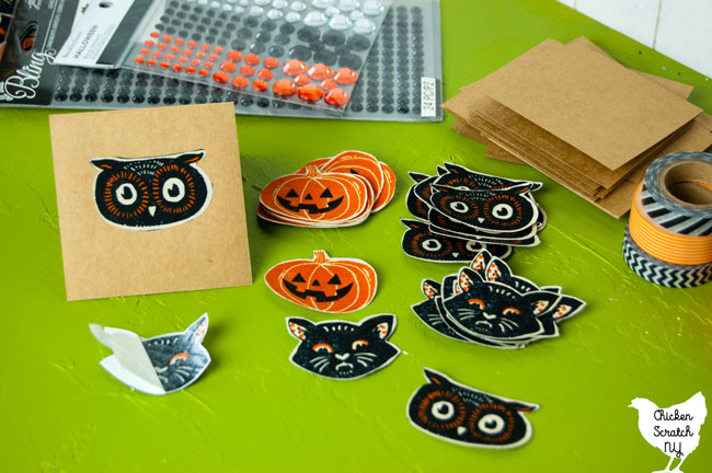 half assembled Halloween banner with kraft paper not card with fabric cat face attached next to piles of cut out Halloween fabric shapes