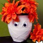 mummy vase made out of a dollar store vase covered in strips of muslin with two googley eyes filled with fake orange flowers