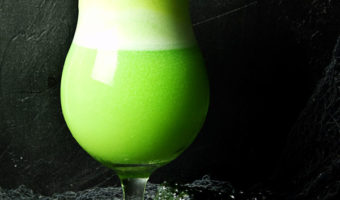 lime sherbet, pineapple and lemon lime soda float in a tall ice cream glass with a black frog in the bottom right corner on a green surface with grey creepy netting and a black background