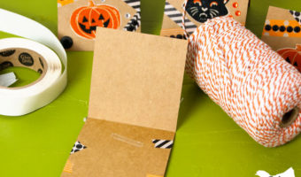 open notecard with glue line inside with orange Bakers twine in the background along with decorated note cards