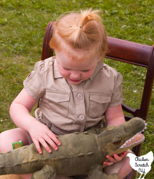 young blonde girl in a khaki saffri shirt hugging a stuffed crocodile dressed like Steve Irwin