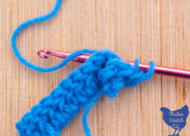 crocheting around the post to the back in blue super saver yarn