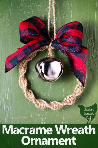 Macramé wreath ornament made with twine, silver bell and and buffalo check ribbon