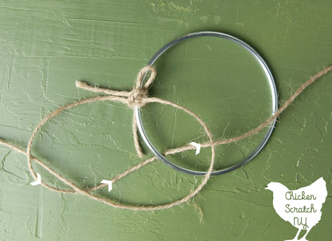 metal ring with twine tied to it to make a macrame half knot