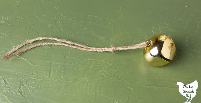 gold bell threaded onto twine and tied in a knot