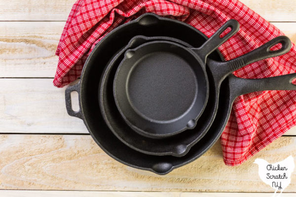 Stack of cast iron skillets on a wooden cutting board with a red checked dish towel