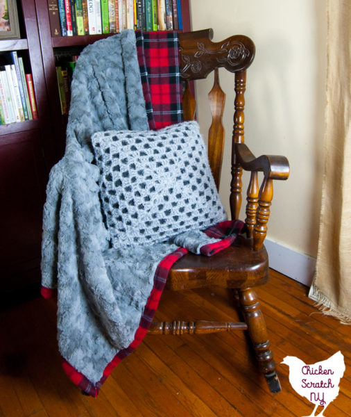 grey fur and red plaid flannel blanket sitting on a rocking chair with a crocheted pillow cover