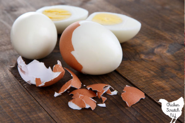 Three hard boiled eggs, one fully shelled and cut in half, two partial peeled with brown egg shell pieces on a wooden surface