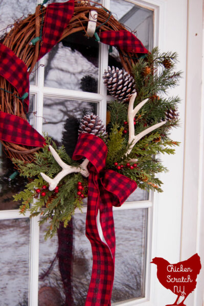 rustic country Christmas wreat with antlers, pine cones and buffalo check ribbon