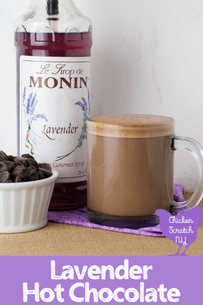 clear glass mug filled with lavender hot chocolate on a rough burlap surface with a bottle of lavender syrup and a ramekin of chocolate chips