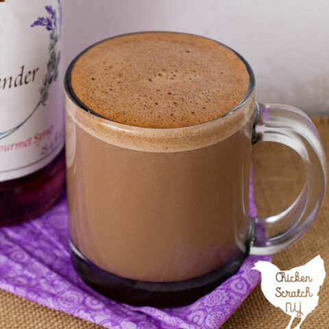 clear glass mug filled with lavender hot chocolate on a rough burlap surface with a bottle of lavender syrup