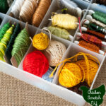 white plastic case filled with various colors of embroidery floss wound into balls, around cardboard squares and plastic bobbins