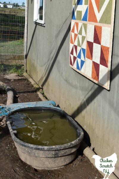 filled water tub next to barn quilt