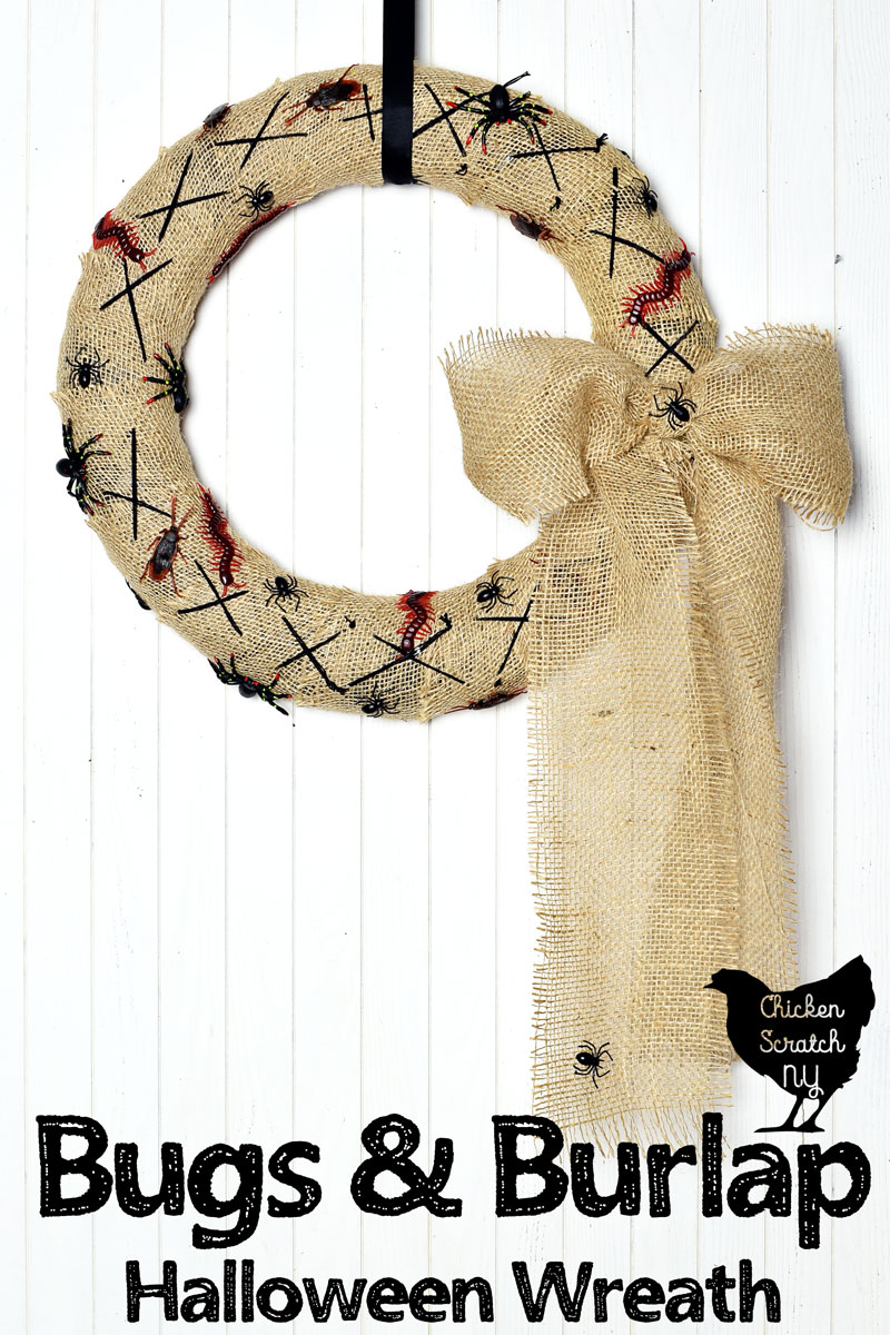 burlap covered Halloween wreath with fake bugs and spiders with a burlap bow hanging on a white wall with a black ribbon