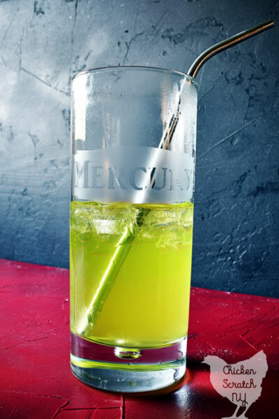 tall glass with mercury etched on the front filled with green liquid and a metal straw