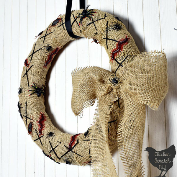 close up of burlap covered Nightmare Before Christmas Wreath with fake bugs and spiders with a burlap bow hanging on a white wall with a black ribbon