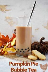 tall glass filled with cramy tan tea with black boba pearls, two milano cookies, a wicker pumpkin, fake leaves and a silver bubble tea straw