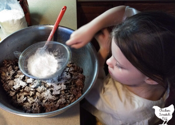 little girl with powdered sugar in a sifter with a large metal bowl filled with muddy buddies
