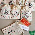 Christmas countdown made with muslin bags, hand numbers with green and red polka dots filled with jokes and hot cocoa packets