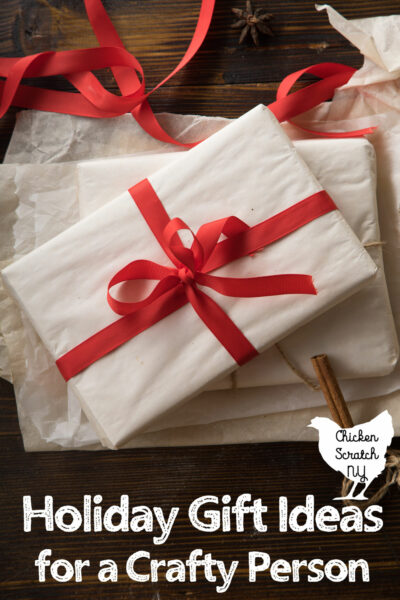 white gift box tied up with red ribbon , text overlay holiday gift ideas for a crafty person