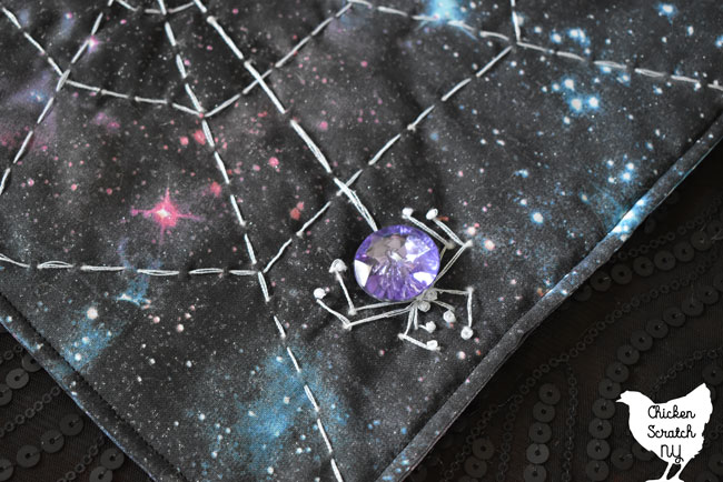 purple crystal button spider on a galaxy print spiderweb mini quilt