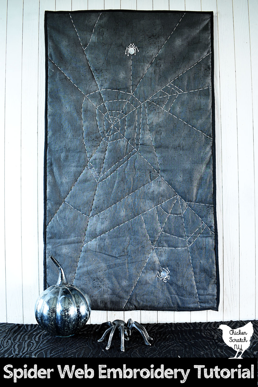 embroidered spiderweb wall hanging with button spiders on a white wall above a black table covered in a sequined table cloth with a mercury glass pumpkin and a cast iron spider