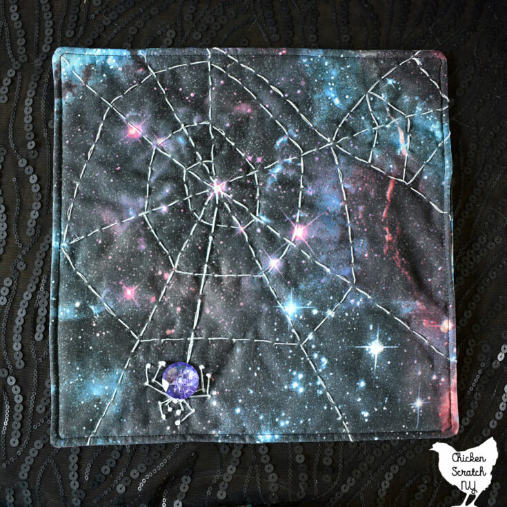 small square spiderweb mini quilt with hand embroidery on galaxy print fabric with a crystal button spider