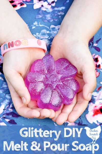 little girls hands holding a purple flower shaped bar of soap with holographic glitter