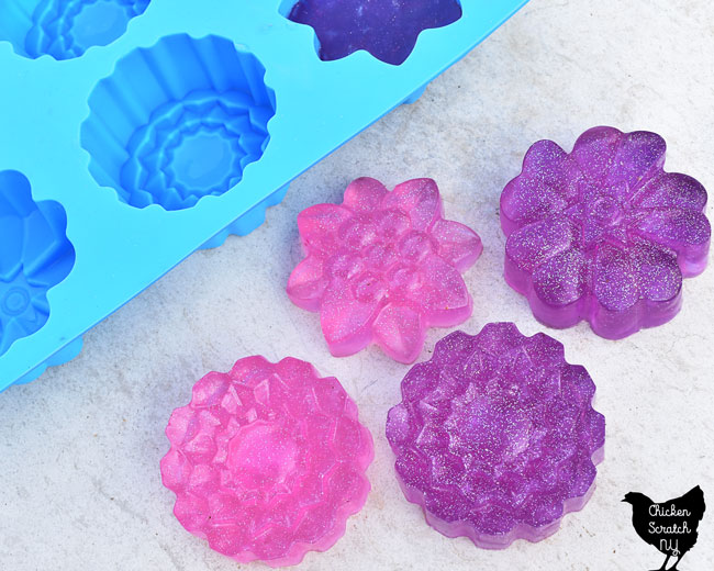 pink and purple melt and pour soap bars made with a floral silicone mold and holographic glitter
