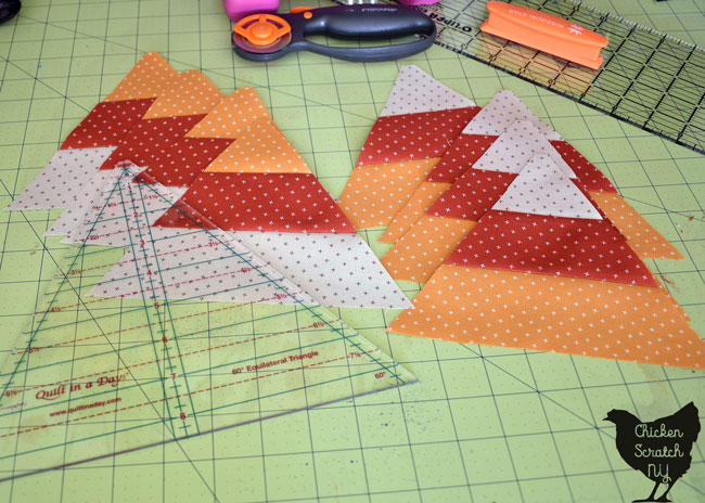 cut 60 degree candy corn triangles in two piles with a 60-degree ruler and rotary cutter on a rotary mat