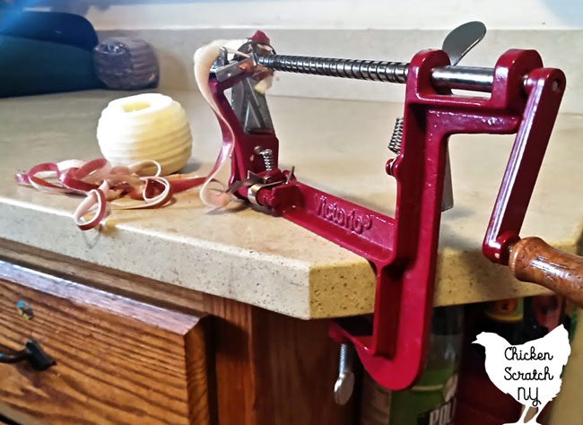 apple peeler corer slicer clamped to counter with peeled apple