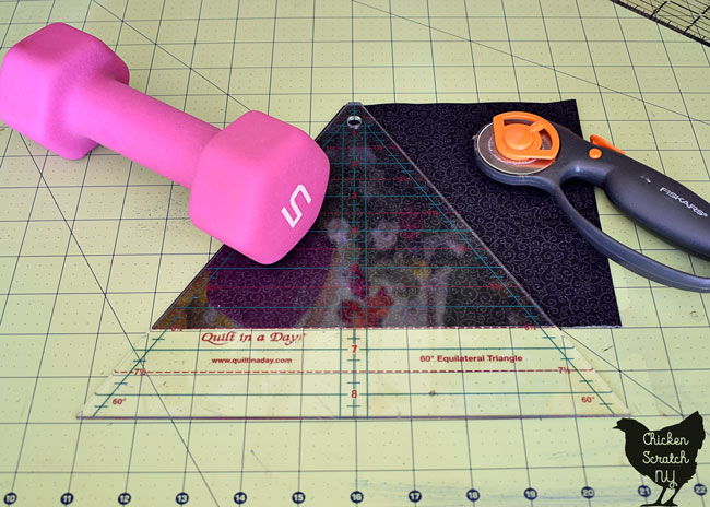 60 degree ruler on black fabric with rotary cutter and weight