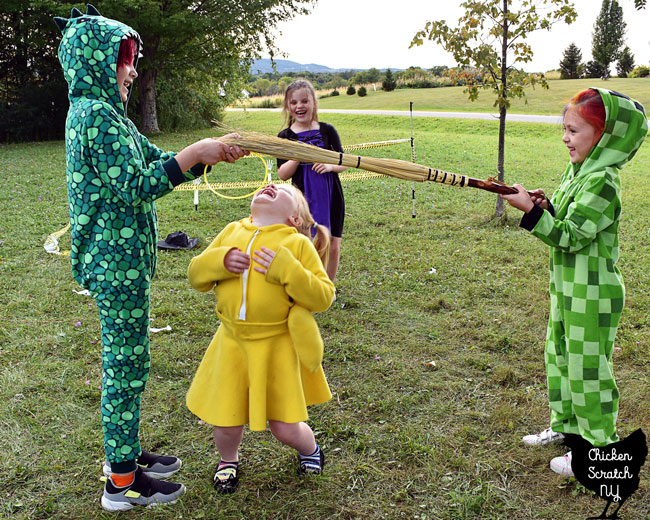 four kids in Halloween costumes playing limbo with a broom stick at a party