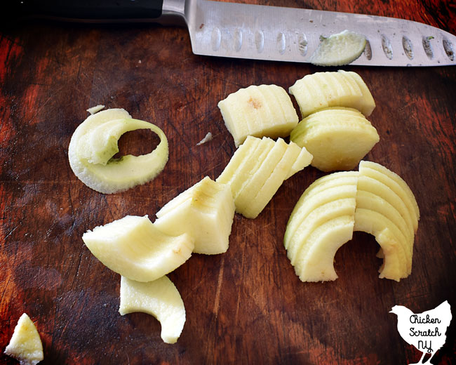 cut apples on a cutting board with a large kitchen knife