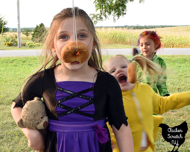 child in witch Halloween Costume playing donut on a string party game