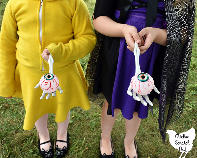 two girls in Pikachu and witch costumes holding plastic eyeballs on skeleton hands for a Halloween Party egg race